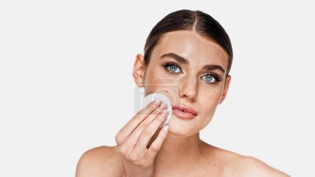 Young woman removing makeup with cotton pad isolated on white