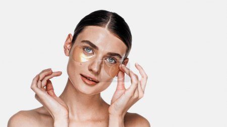 Woman applying eye patches under eyes isolated on white