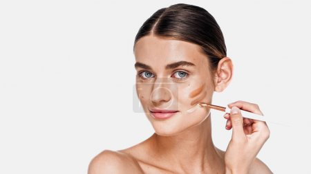 Photo for Young adult woman applying different shades of concealer on cheek isolated on white - Royalty Free Image