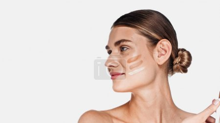 Photo for Young adult woman with shades of face foundation on cheek isolated on white - Royalty Free Image
