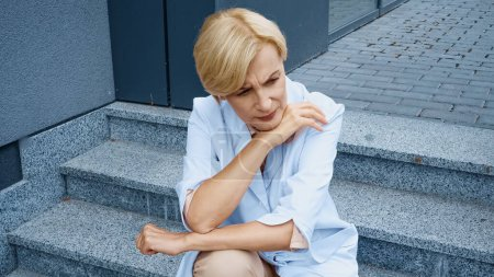 Photo for Tired mature doctor sitting on stairs near clinic - Royalty Free Image