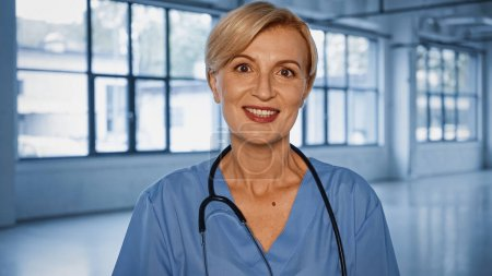 Cheerful doctor with stethoscope looking at camera in clinic