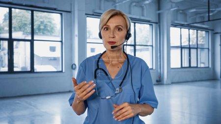 Arzt im Kopfhörer spricht im Krankenhaus vor Kamera