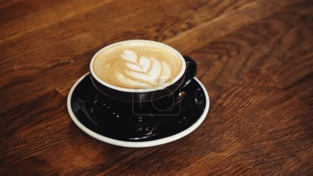 Photo for Cup of delicious cappuccino with latte art on table - Royalty Free Image