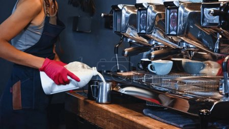 cropped view of barista pouring milk from carton box