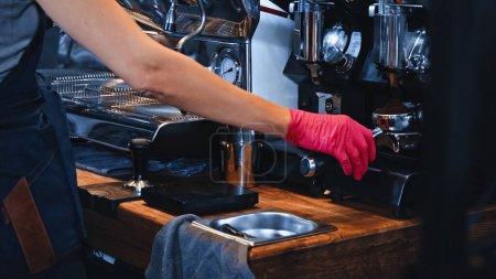 Photo pour Vue recadrée de barista en gant de latex tenant portafilter avec café moulu dans le café - image libre de droit