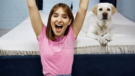 excited woman with raised hands near golden retriever dog in bedroom