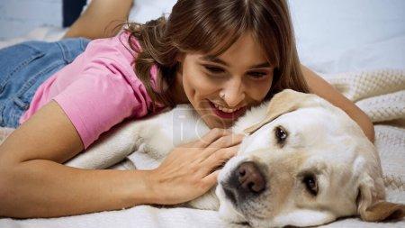 Photo pour Heureux jeune femme couché avec golden retriever chien sur le lit - image libre de droit