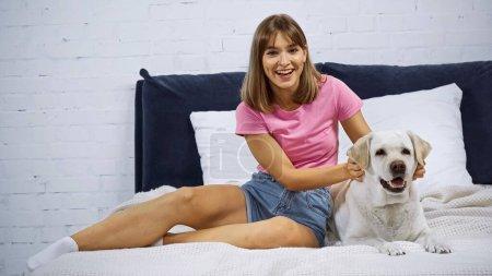 Photo pour Excité jeune femme câlin doré retriever sur lit - image libre de droit