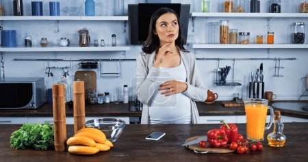 Pensive pregnant woman standing near smartphone and fresh ingredients in kitchen