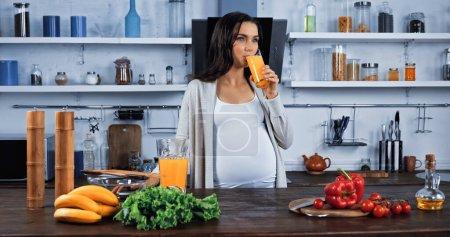 Photo pour Femme enceinte buvant du jus d'orange près des aliments biologiques dans la cuisine - image libre de droit