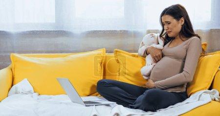 Photo pour Femme enceinte tenant un jouet doux et pleurant tout en regardant un film sur ordinateur portable - image libre de droit