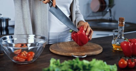 Cropped view of woman holding knife and bell pepper near vegetables on blurred foreground
