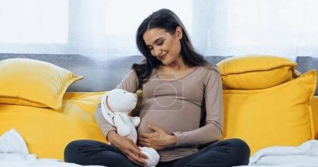 Młoda ciężarna kobieta trzyma miękką zabawkę siedząc na kanapie