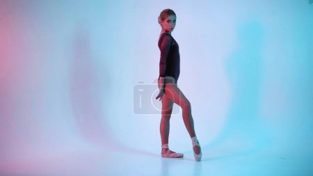 young ballerina dancing and looking at camera on blue background