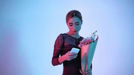 Photo pour Ballerine tenant des fleurs tout en utilisant smartphone sur bleu - image libre de droit