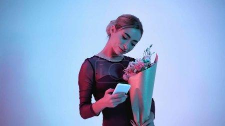 Photo pour Ballerine tenant des fleurs et utilisant un smartphone sur bleu - image libre de droit