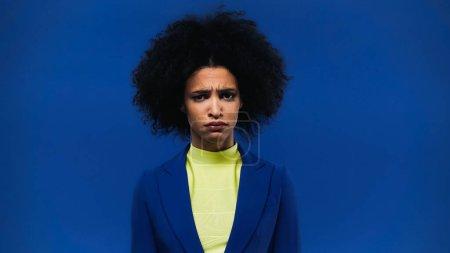 Photo pour Femme afro-américaine bouleversée en veste regardant la caméra isolée sur bleu - image libre de droit