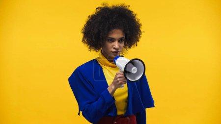 Afroamerikanerin hält Lautsprecher isoliert auf gelb