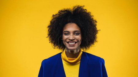 Positive african american woman in blue blazer looking at camera isolated on yellow
