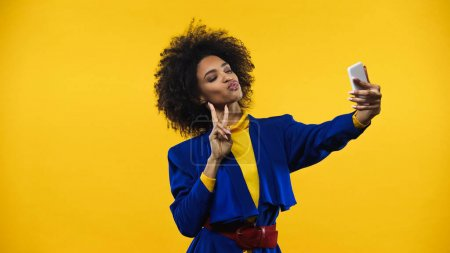 Photo for African american woman showing peace sign during selfie isolated on yellow - Royalty Free Image