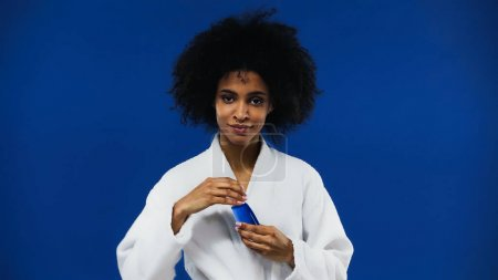 Photo for African american woman in bathrobe holding lotion isolated on blue - Royalty Free Image