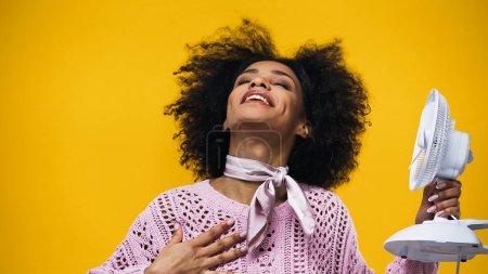 Photo pour Heureuse femme afro-américaine tenant un ventilateur électrique isolé sur jaune - image libre de droit