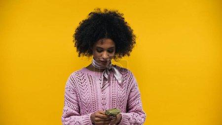 Photo pour Femme afro-américaine tenant des dollars isolés sur jaune - image libre de droit