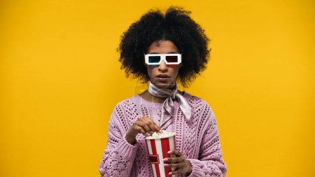 African american woman in 3d glasses holding popcorn isolated on yellow