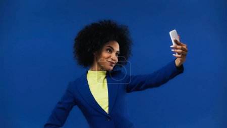 Smiling african american woman taking selfie isolated on blue