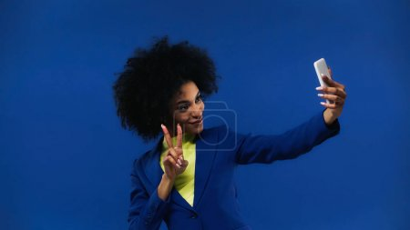 Photo for Smiling african american woman showing peace sign and taking selfie isolated on blue - Royalty Free Image