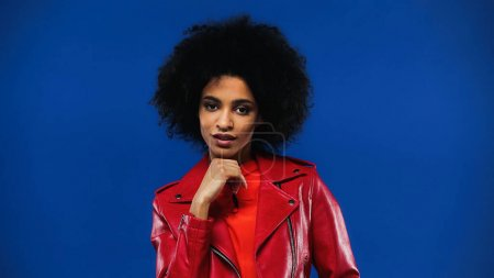 Curly african american woman in red jacket looking at camera isolated on blue