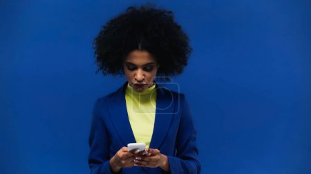 Young african american woman using smartphone isolated on blue