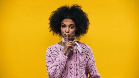 Photo pour Jeune femme afro-américaine montrant un signe secret isolé sur jaune - image libre de droit