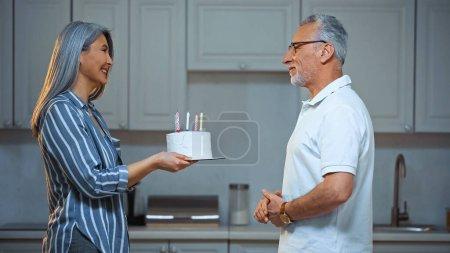 Photo pour Vue latérale de senior asiatique femme donnant gâteau d'anniversaire à heureux mari - image libre de droit