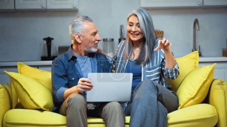 Photo pour Gai asiatique femme geste tout en parlant à mari près ordinateur portable à la maison - image libre de droit