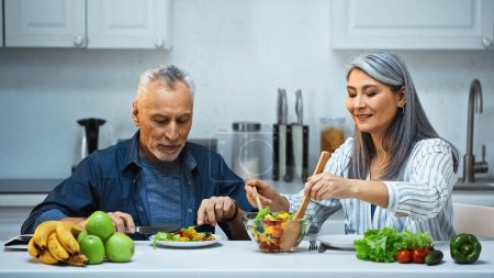 Photo for Smiling asian woman mixing salad near elderly husband having breakfast in kitchen - Royalty Free Image