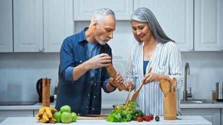 Senior Mann hält Gewürzmühle in der Nähe glücklich asiatische Frau bereitet Salat zum Frühstück