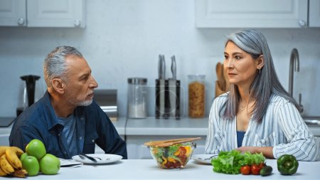 elderly interracial couple looking at each other during breakfast in kitchen