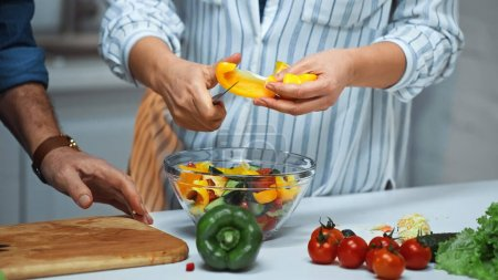 Photo for Partial view of senior woman cutting bell pepper near husband in kitchen - Royalty Free Image