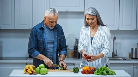 Foto de Pareja interracial de ancianos preparando ensalada fresca para el desayuno en la cocina - Imagen libre de derechos