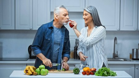 Foto de Feliz mujer asiática alimentación marido con pimiento mientras se prepara el desayuno en la cocina - Imagen libre de derechos