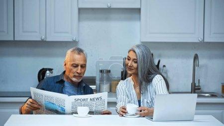 lächelnde asiatische Frau schaut älteren Mann beim Zeitungslesen in der Küche an