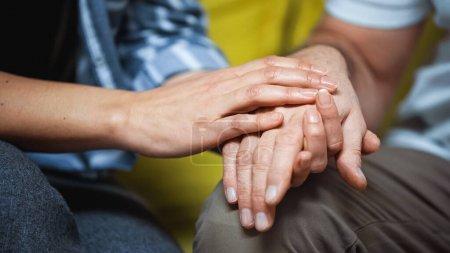 abgeschnittene Ansicht einer Frau, die die Hand ihres älteren Mannes berührt, verschwommener Hintergrund