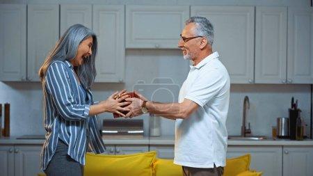 Photo pour Vue latérale de excité asiatique femme prise cadeau boîte de heureux mari aîné - image libre de droit