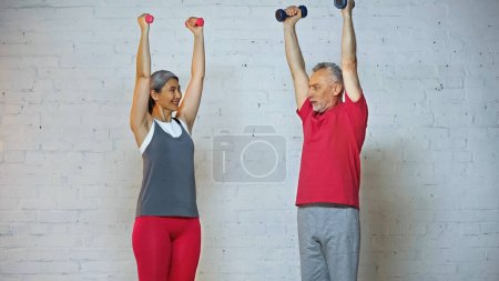 smiling asian woman looking at senior husband while training with dumbbells