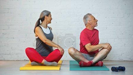 Photo pour Sportif senior interracial couple méditant sur tapis de fitness en pose de lotus - image libre de droit