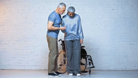 senior man supporting handicapped asian wife near wheelchair