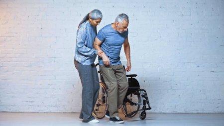 Photo pour Femme asiatique âgée soutenant mari handicapé près de fauteuil roulant - image libre de droit