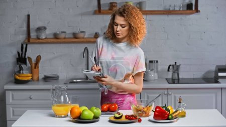 woman writing in notebook and weighing tomatoes near vegetables and orange juice on table